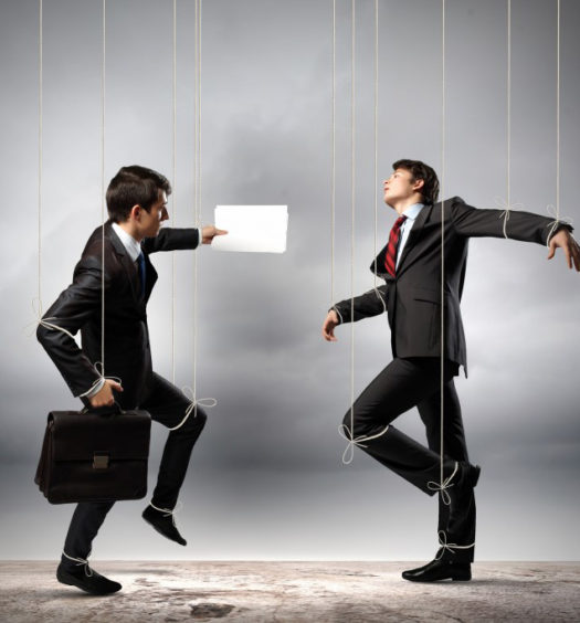 Photograph depicting businessmen as puppets on string to emphasize the problems of micromanagement.